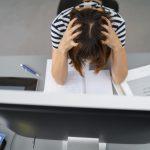 Verzweifelte Doktorandin rauft sich die Haare vor dem Computer